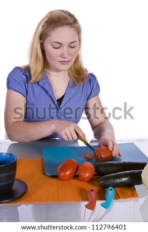 Beautiful Girl  in the Kitchen Cutting Tomatoes and Cucumber while haveing Wine