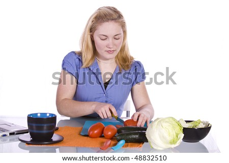 Beautiful Girl  in the Kitchen Cutting Tomatoes and Cucumber while having Wine