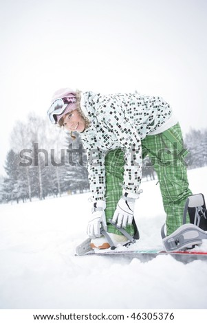 Beautiful girl in the mountains snowboarding clothes