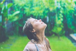 beautiful girl in the rain . Wet hair and shirt . Tropical rain
