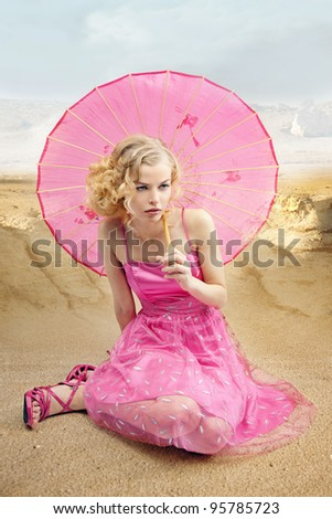 beautiful girl in the sand of desert with the sun umbrella