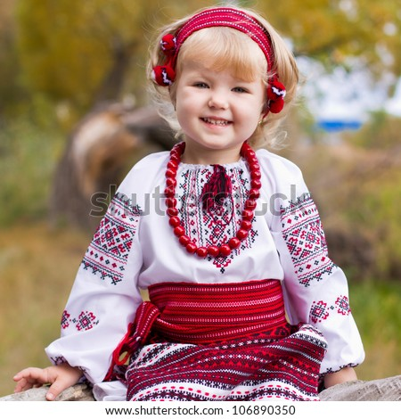 Beautiful girl in ukrainian costume sitting on a log outdoor
