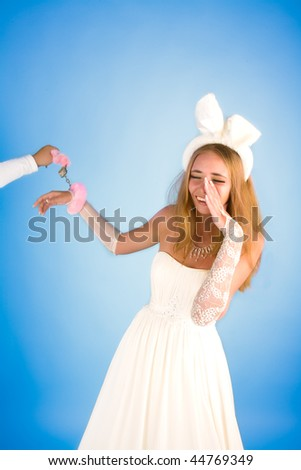 Beautiful girl in wedding dress and rabbit's ears smiling