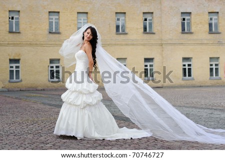beautiful girl in wedding dress with long tule train standing alone