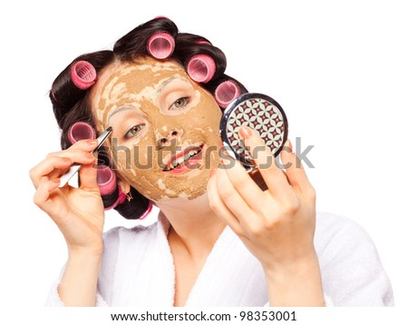 Beautiful girl in white bath robe with clay facial mask and curler pull out eyebrows. Isolated background