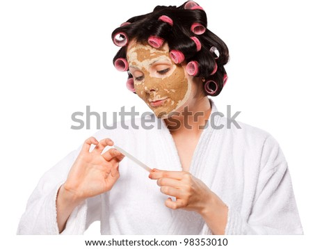 Beautiful girl in white bath robe with clay facial mask and curlers taking care of nails
