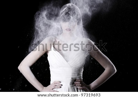 Beautiful girl in white dress and flying dust over black background
