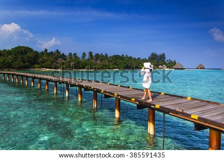 Beautiful girl in white dress and hat standing on wooden planks in the Maldives island on the background of a bungalow on the water and the beauty of the sea with the coral reefs #385591435