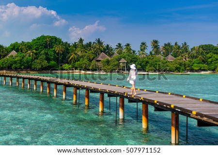 Beautiful girl in white dress and hat standing on wooden planks in the Maldives island on the background of a bungalow on the water and the beauty of the sea with the coral reefs #507971152
