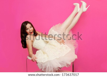Beautiful girl in white dress having fun on the table. Holiday, wedding, shopping, pin up - concept