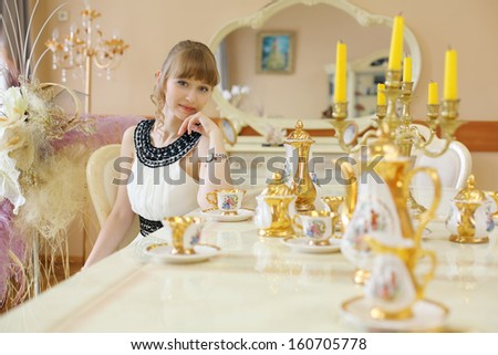 Beautiful girl in white dress sits at table with set of dishes and dreams.