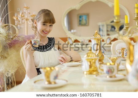 Beautiful girl in white dress sits at table with set of dishes and holds cup of tea.