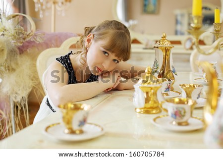 Beautiful girl in white dress sits at table with set of dishes and looks at camera.