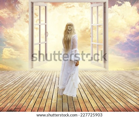 beautiful girl in white dress standing looking into open window dreamland day light surreal sky skyline view. Positive human emotion feeling happiness life perception success peace of mind concept