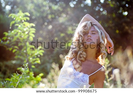 Beautiful  girl  in  white dress walking on the meadow in summer day