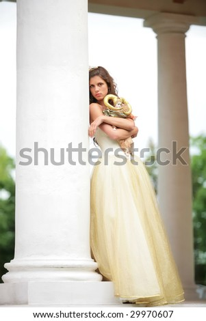 beautiful girl in white-golden dress with loved doll dreams of future