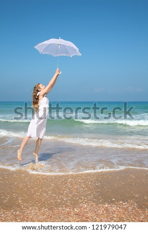 Beautiful girl in white on the beach with umbrella