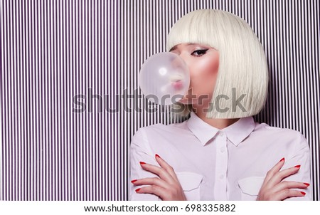 Beautiful girl in white wig blew up in pink gum bubble. A young girl in the studio on a background of a black and white vertical lines. Stylish girl wearing a white shirt. #698335882