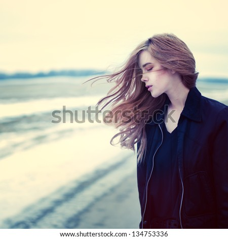 Stock Photo beautiful girl in windy conditions on the road in a field
