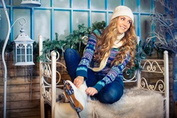 Beautiful girl in winter clothes puts on skates