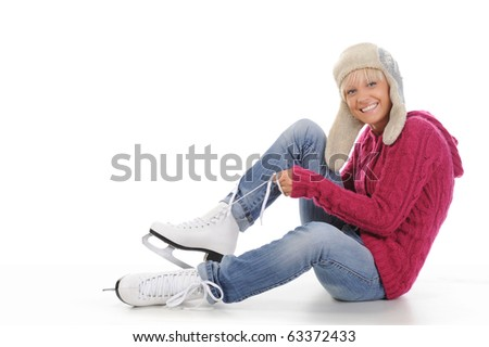 Beautiful girl in winter clothes puts on skates. Isolated on white background