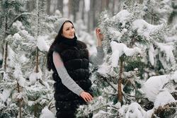 Beautiful girl in winter fur vest walking in snowy winter forest in cold day.