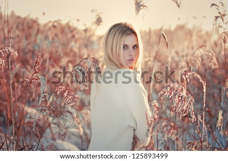 beautiful girl in winter in the high grass. Photos in golden color