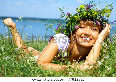 beautiful girl in wreath of flowers lay in meadow on sunny day