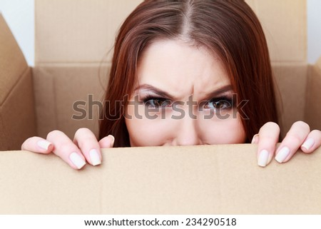 Beautiful girl inside a cardboard box. Difficult crossing concept. Emotions concept. Anger. Unexpected gift concept