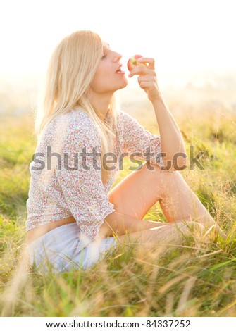 Beautiful girl is eating apple while sitting on green field