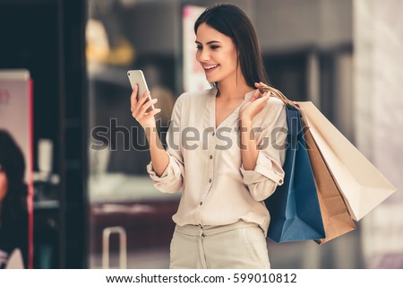 Beautiful girl is holding shopping bags, using a smart phone and smiling while doing shopping in the mall