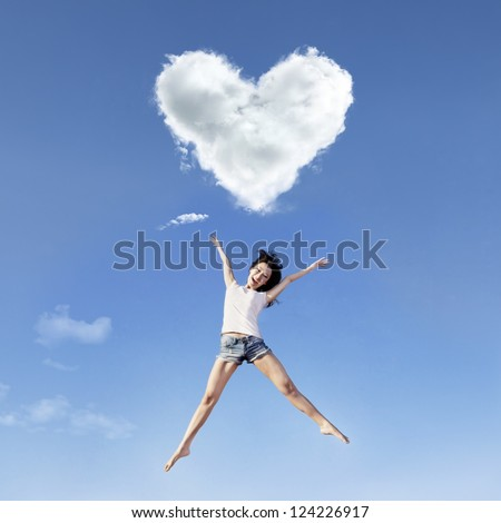 Beautiful girl is jumping under a heart shape cloud