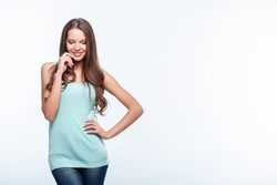 Beautiful girl is looking down with shyness. She is smiling and touching her face with her hand. Isolated on background and copy space in left side