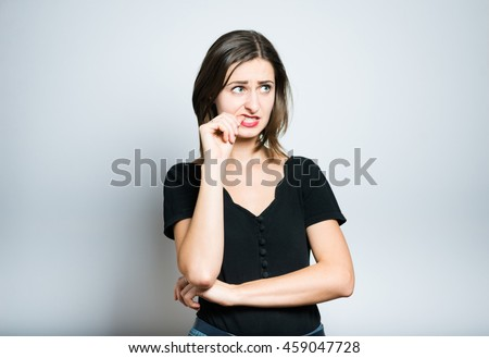 beautiful girl is nervous and bites nails, studio photo isolated on a gray background
