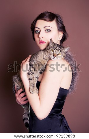 Beautiful girl is posing with her cat. Vintage shoot.