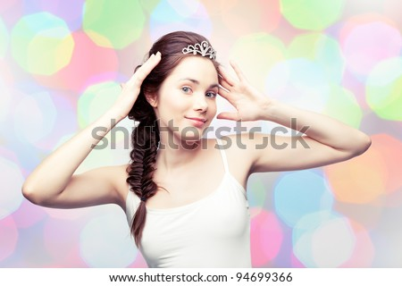 Beautiful girl is putting on a diamond tiara and admiring herself, colorful pastel background