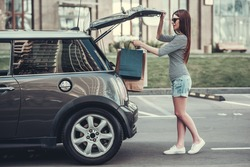 Beautiful girl is putting shopping bags into car trunk and smiling
