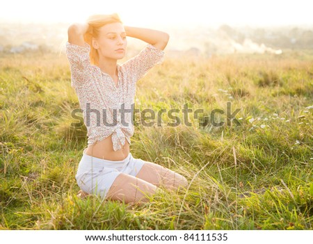 Beautiful girl is relaxing while sitting on green field