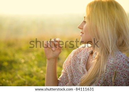 Beautiful girl is relaxing while sitting on green field and biting straw