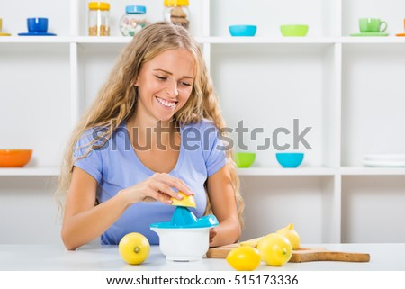 Beautiful girl is sitting at the table at her home and making lemonade.Beautiful girl making lemonade
