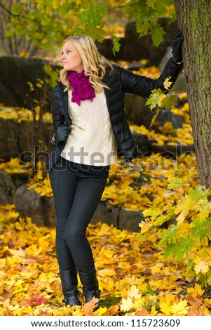 Beautiful girl leans on tree, several leaves on the ground