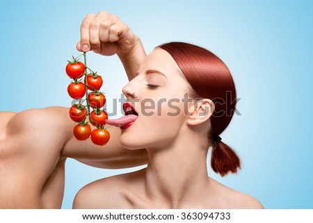Beautiful girl licking ripe red cherry tomatoes on the vine sexually with her seductive tongue; foreplay with food and feeding on blue background.