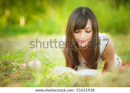 Beautiful girl lies on meadow and reads the book