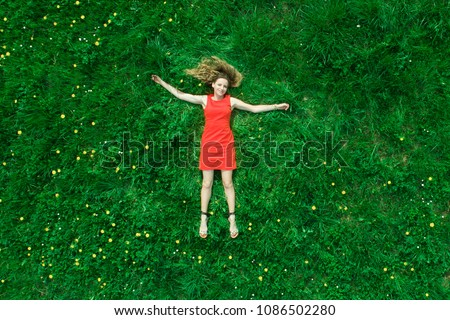 Beautiful girl lies on the grass in nature and smiles. Top view. Long shot. Summer concept. Foto stock ©