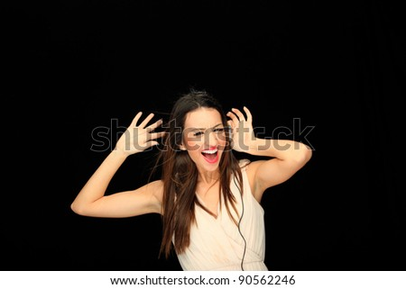 Beautiful Girl listening music with headphones over black background