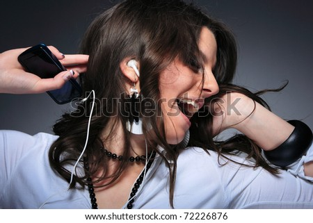 Beautiful Girl listening music with her cell phone over gray background