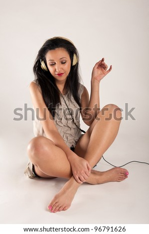 Beautiful girl listening to music against white background.