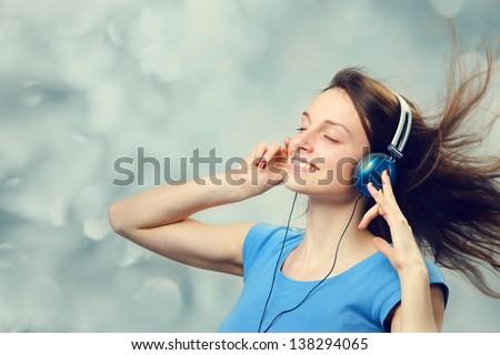 Beautiful girl listening to music on headphones