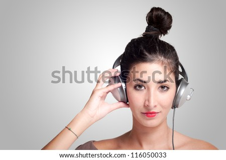 beautiful girl listening to music with headphones on gray background