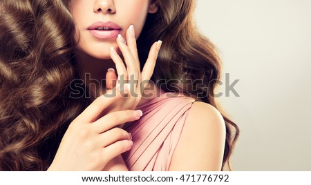 Beautiful girl  long , thick curly hair . Model showing a French manicure on nails .